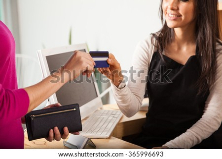 Closeup of a young woman working at a cash register taking a credit card from a customer - stock photo