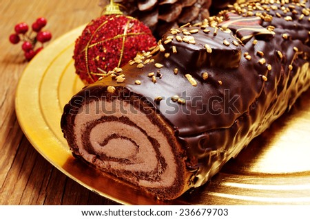closeup of a yule log cake, traditional of christmas time, in a golden tray on a rustic wooden table - stock photo