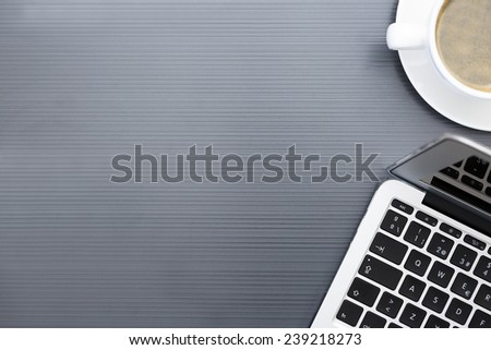 closeup of a zenithal view of a laptop and a white cup of coffee on a grey desk background - suitable for copy space - stock photo