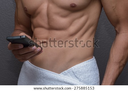 Closeup of abs and chest of sexy muscular Caucasian man with white towel around waist holding cell phone in one hand as he texts or dials - stock photo