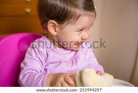 Closeup of adorable happy baby laughing and playing with teddy bear sitting in a feeding chair at home - stock photo