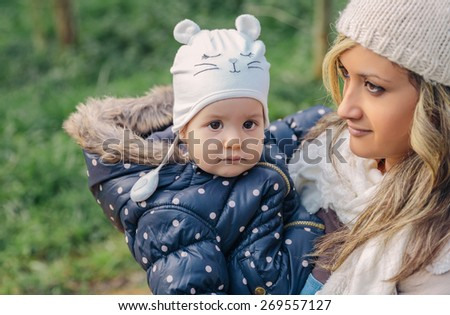 Closeup of adorable little girl with hat in the hands of her young mother over a nature background - stock photo