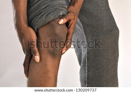 Closeup of African American man clutching injured knee - stock photo