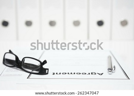 closeup of agreement, glasses and pen with binders in blurred background. Legal  and law concept - stock photo