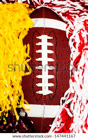 Closeup of American football and pom poms. - stock photo