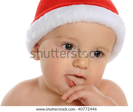 Closeup of an adorable baby boy in Santa's hat, contemplating Christmas events.  Isolated on white. - stock photo