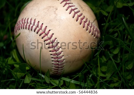 Closeup of an aged and worn hardball or baseball laying in the green grass. Shallow depth of field. - stock photo