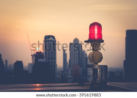 Closeup of an aircraft warning light on top of a highrise of building in evening time. for  safety concept - stock photo
