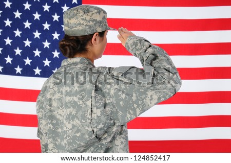 Closeup of an American Female Soldier in combat uniform saluting a flag. Seen from behind horizontal format with the flag filling the frame. - stock photo