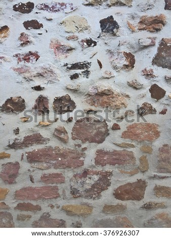 Closeup of an ancient irregular bricks wall with varicouloured elements  - stock photo