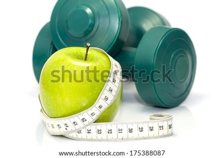 Closeup of an apple with a measuring tape around it and  dumbbells at the background - stock photo