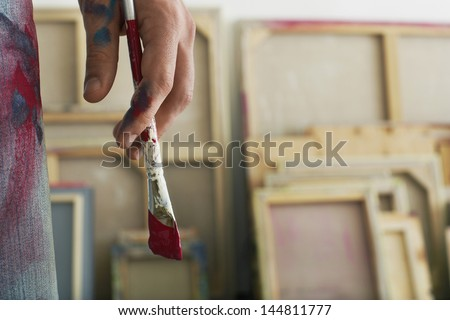 Closeup of an artist holding paintbrush - stock photo
