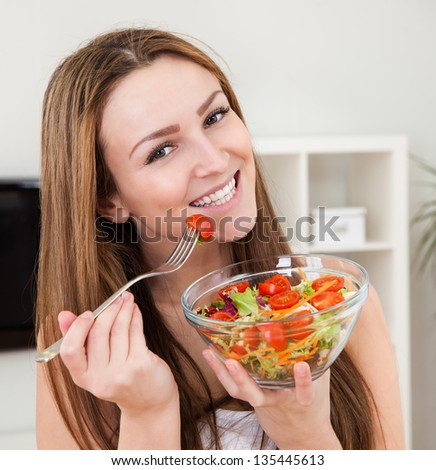 Closeup Of An Attractive Young Woman Eating Fruit Salad - stock photo