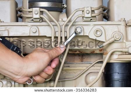 Closeup of an auto mechanic working on a Generator power engine - stock photo