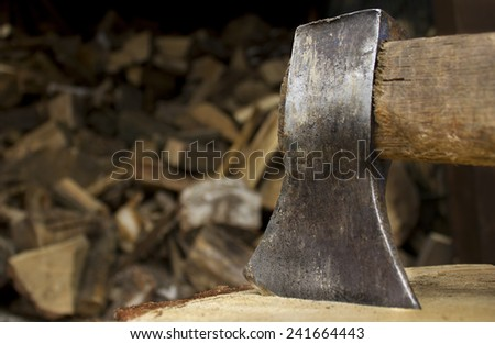 Closeup of an axe sticking in a chunk of firewood in front of a staple of firewood. - stock photo