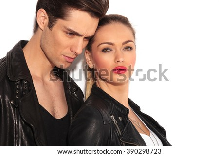 closeup of an embraced young couple in leather jackets, woman is looking at the camera - stock photo