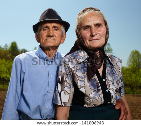 Closeup of an old farmers couple outdoor - stock photo