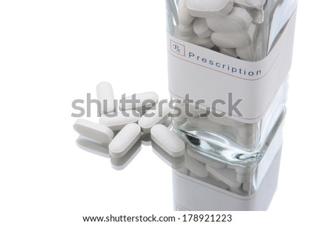 Closeup of an old fashioned medicine bottle standing on a white reflective surface.  The bottle has a blank prescription label and pills laying on the surface. - stock photo