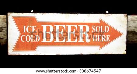 Closeup of an Orange and White Sign indicating the Direction to the Bar - Ice Cold Beer Sold Here - stock photo