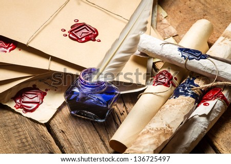 Closeup of ancient scrolls and old envelope with blue inkwell - stock photo