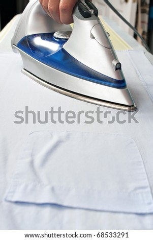 Closeup of and iron pressing and ironing a pocketed dress shirt on an ironing board. - stock photo