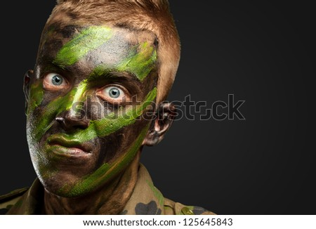 closeup of angry soldier with painting against a black background - stock photo