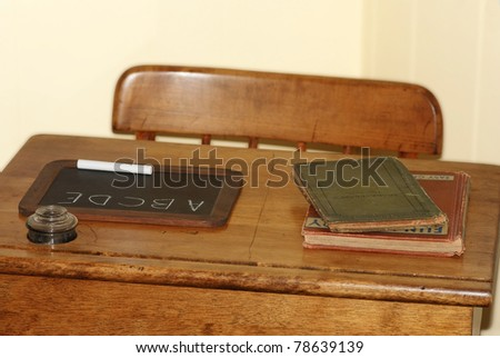 Closeup of antique school desk and chair with small chalk board, some old books and an ink well against pale yellow background. - stock photo