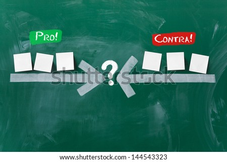 Closeup of arrows pointing at question mark with sticky notes on blackboard representing pros and cons - stock photo