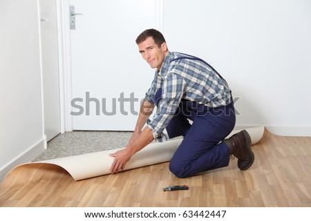 Closeup of artisan installing ground floor in room - stock photo