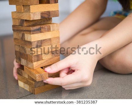 Closeup of Asian kid's hand playing wood blocks stack game  - stock photo