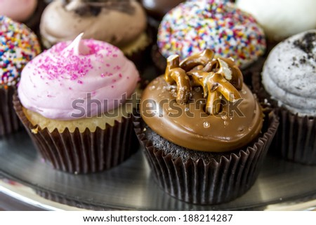 Closeup of assorted flavors of decorated cupcakes sitting on silver platter - stock photo