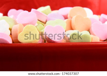 Closeup of assorted pastel candy hearts for Valentines Day in a red ceramic candy bowl. Shallow depth of field. The candies are blank and ready for you to add your own message. - stock photo