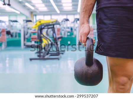 Closeup of athletic man holding black iron kettlebell in a crossfit training on fitness center - stock photo
