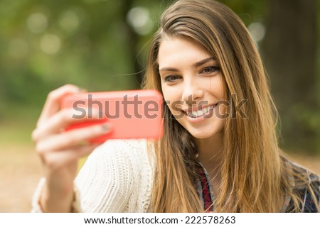 Closeup of attractive young Caucasian woman taking a selfie with smartphone outdoors in park in autumn. Beautiful blonde teenage girl taking a self portrait in nature in fall. - stock photo