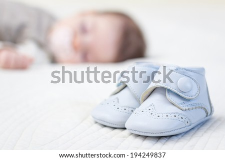 Closeup of baby blue leather shoes over a bed and adorable babe sleeping on the background - stock photo