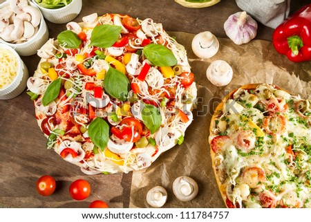 Closeup of baked and raw pizza with fresh ingredients - stock photo