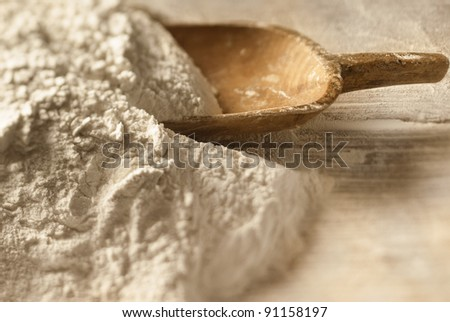 Closeup of baking powder and a wooden scoop - stock photo