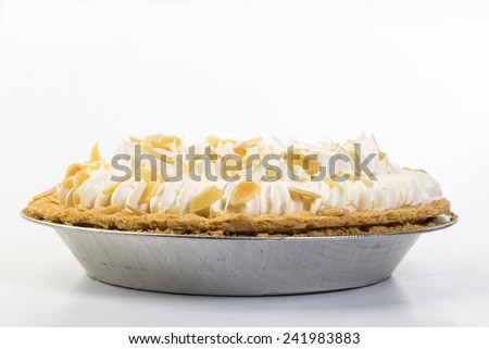Closeup of banana cream pie sprinkled with chopped almonds.  Aluminum baking pan against white background with copy space. - stock photo