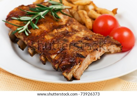 Closeup of barbecued pork ribs and vegetables - stock photo