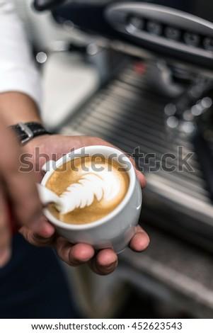 Closeup of barista pouring milk into art cappuccino - stock photo