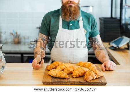 Closeup of bearded man in white apron with tattoo on hands standing in cafe and holding tongs for croissants - stock photo