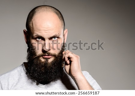 Closeup of bearded man touching his beard while standing against white background - stock photo
