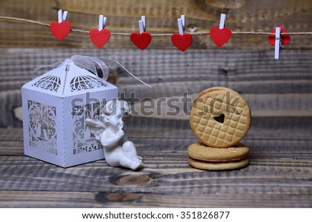 Closeup of beautiful cupid angel decorative figurine near white paper greeting valentine box and red hanging clothes-peg with round cookie on wooden background, horizontal picture - stock photo