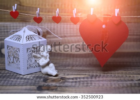 Closeup of beautiful cupid angel decorative figurine near white paper greeting valentine box and red card on hanging ribbon on clothes-peg with no people on wooden background copy space, horizontal - stock photo