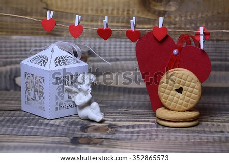 Closeup of beautiful cupid angel decorative figurine near white paper greeting valentine box and red card on hanging ribbon on clothes-peg with round cookie on wooden background, horizontal picture - stock photo