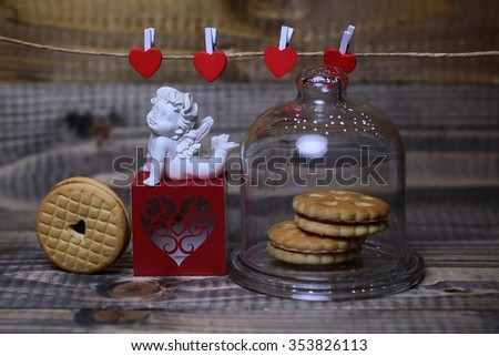 Closeup of beautiful cupid angel decorative figurine on red paper greeting valentine box and hanging clothes-peg with round cookie under glass flask on wooden background, horizontal picture - stock photo