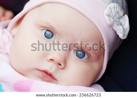 Closeup of beautiful cute little girl is in carriage with big blue eyes - stock photo
