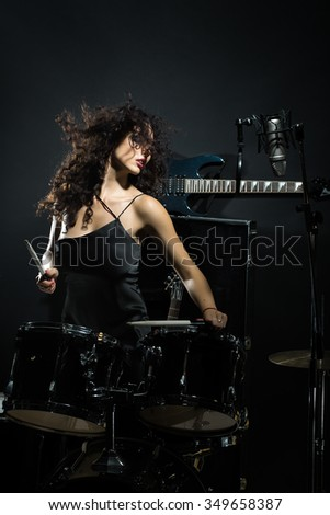 Closeup of beautiful emotional expressive cool young brunette sexual rock musician woman with long curly hair standing in recording studio playing drums with sticks near electro guitar and microphone - stock photo