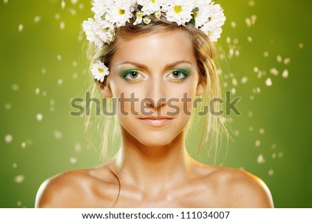 Closeup of beautiful female with green makeup and white flower wreath - stock photo