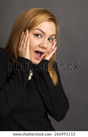 Closeup of beautiful girl with astonished expression over gray background - stock photo